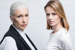 Portrait of serious women standing together and looking at camera. Young and senior people royalty free stock image
