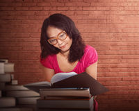 Portrait of a serious young asian woman reading a book Stock Images