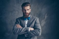 Portrait of serious young bearded man with mustache in a suit st. Ands on a gray background with folded his hands and fixedly looks royalty free stock photos