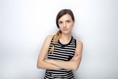 Portrait of serious young beautiful woman in striped shirt crossed hands posing for model tests against studio background Stock Photos