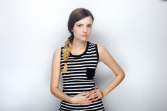 Portrait of serious young beautiful woman in striped shirt incredulous looking into camera posing for model tests against studio b Royalty Free Stock Photos