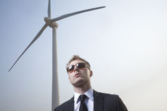 Portrait of serious young businessman in sunglasses standing by a wind turbine Royalty Free Stock Photos