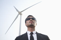 Portrait of serious young businessman in sunglasses standing by a wind turbine Stock Images
