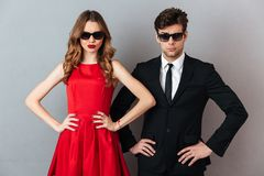 Portrait of a serious young couple dressed in formal wear. And sunglasses standing and looking at camera over gray wall background Stock Images