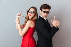 Portrait of a serious young couple dressed in formal wear. And sunglasses standing back to back and showing gun gesture over gray wall background Royalty Free Stock Image