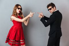 Portrait of a serious young couple dressed in formal wear. And sunglasses standing and showing gun gesture over gray wall background Royalty Free Stock Images