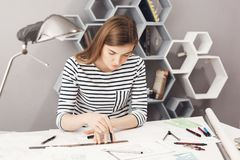 Portrait of serious young good-looking female architect sitting at her workplace, making drawings with pencil and ruler. Trying not to make a mistake in stock photography