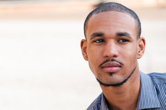 Portrait of a Serious Young Man. Close up portrait of a serious, attractive, young African American male in his twenties.  Horizontal.  Copy space Royalty Free Stock Photo