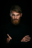 Portrait of serious young man with folded and crossing hands sta. Nding  on black background and looking at camera Confident concept Stock Image