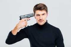 Portrait of serious young man put gun to temple Royalty Free Stock Image
