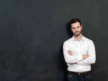 Portrait of a serious young man standing against chalkboard stock images