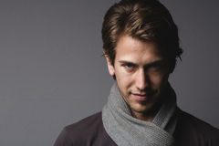 Young man in scarf. Portrait of serious young man wearing knitted woolen scarf with copy space on gray background Royalty Free Stock Photography