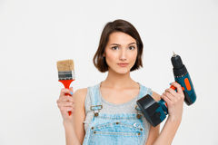 Portrait of serious young pretty girl, holding painting brush Stock Photography