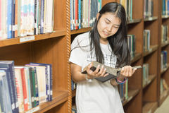 Portrait of a serious young student reading a book in a library. Beautiful female student in a university library Royalty Free Stock Photo