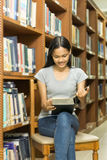 Portrait of a serious young student reading a book in a library. Beautiful female student in a university library Royalty Free Stock Photography