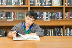 Portrait of a serious young student reading a book in a library. Serious male student reading a book in a library Stock Photography