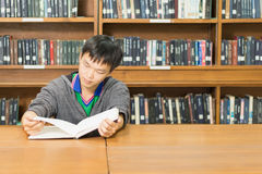 Portrait of a serious young student reading a book in a library. Serious male student reading a book in a library Royalty Free Stock Images