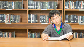 Portrait of a serious young student reading a book in a library. Serious male student reading a book in a library Stock Image