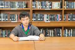 Portrait of a serious young student reading a book in a library. Serious male student reading a book in a library Stock Photo