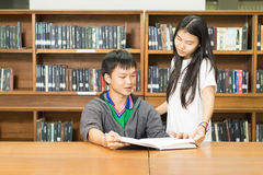 Portrait of a serious young student reading a book in a library. People, knowledge, education and school concept - happy student  with book in library Royalty Free Stock Photography
