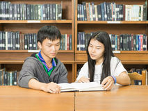 Portrait of a serious young student reading a book in a library. People, knowledge, education and school concept - happy student  with book in library Royalty Free Stock Image