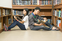 Portrait of a serious young student reading a book in a library. People, knowledge, education and school concept - happy student  with book in library Stock Image