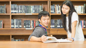 Portrait of a serious young student reading a book in a library. People, knowledge, education and school concept - happy student  with book in library Royalty Free Stock Images