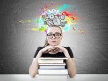 Serious blonde student, books, cog brain stock photography