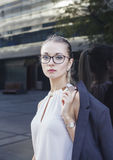 Portrait of serious young woman with glasses. Vertical portrait of serious young woman in suit with glasses and watch. Business concept Royalty Free Stock Images