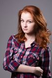 Portrait of a serious young woman in a plaid shirt Stock Image