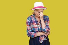 Portrait seulement de femme m?re d?prim?e triste dans le style occasionnel avec la position de chapeau, maintenant la t?te et ple images libres de droits
