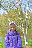 Portrait of the seven-year-old girl against the background of the blossoming birch of useful Himalaya Betula utilis D.Don stock image