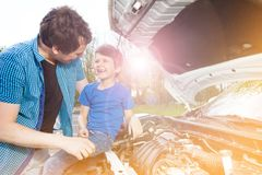 Happy father and son repairing car outside stock photo