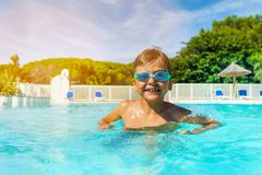 Boy with swimming goggles standing in outdoor pool Royalty Free Stock Photography