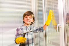 Happy boy washing windows with sponge and brush Royalty Free Stock Images