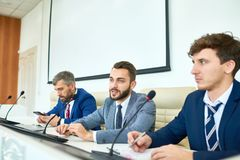 Bearded Politician Speaking in Press Conference. Portrait of several business people sitting in row participating in political debate during press conference stock photo