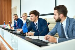 Young Politician Speaking in Political Debate. Portrait of several business people sitting in row participating in political debate during press conference royalty free stock image