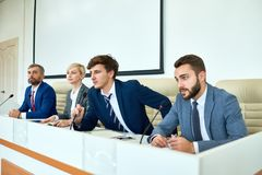 Young Politician Speaking in Press Conference. Portrait of several business people sitting in row participating in political debate during press conference stock photos