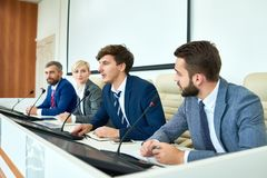 Young Politician Speaking in Press Conference. Portrait of several business people sitting in row participating in political debate during press conference royalty free stock photography