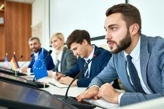 Bearded Politician Speaking in Press Conference. Portrait of several business people sitting in row participating in political debate during press conference royalty free stock image