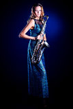 Romantic. Portrait of a sexual young woman posing with saxophone at studio Stock Photos