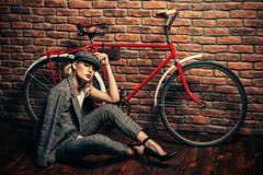 Girl and bike. Portrait of a sexual young woman wearing checkered suit, cap and glasses. Beautiful smart girl. Beauty, fashion royalty free stock photo