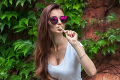 Portrait of sexual young women in glasses which licks a lollipop stock images
