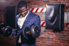 Healthy african man working out with dumbbells in gym. Portrait Sexy african man in classic suit working out with dumbbells in gym Stock Photo