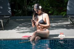 Asian girl play smartphone in pool. Portrait of Asian beautiful woman with black two piece swimsuit and sunglasses play social media, chat, or video call by stock image