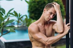 Portrait of sexy athletic man in white pants with naked torso resting in tropical garden. With. Fitness model posing on camera stock photography