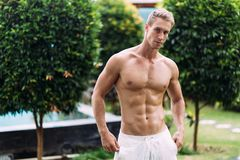 Portrait of sexy athletic man in white pants with naked torso resting in tropical garden. With. Fitness model posing on camera stock image