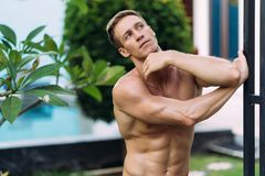 Portrait of sexy athletic man in white pants with naked torso resting in tropical garden. With. Fitness model posing on camera royalty free stock photos
