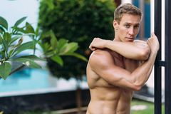 Portrait of sexy athletic man in white pants with naked torso resting in tropical garden. With. Fitness model posing on camera royalty free stock images