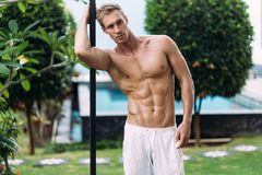 Portrait of sexy athletic man in white pants with naked torso resting in tropical garden. With. Fitness model posing on camera stock photos